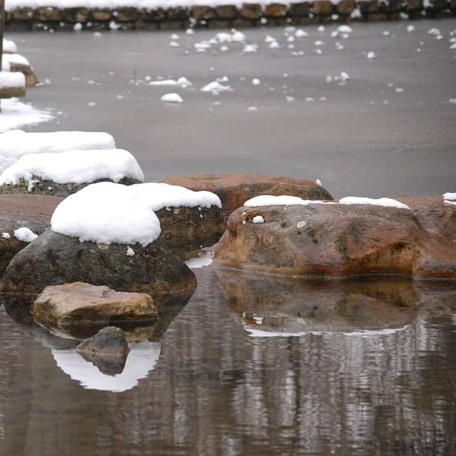 A garden fish pond with rocks in winter