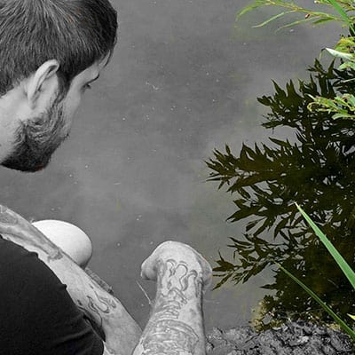 A man sitting by a pond to build trust and familiarity with his koi