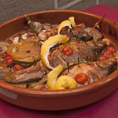 Cooked tench fish with lemons and vegetables
