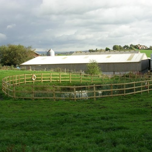 A fenced pond in a field
